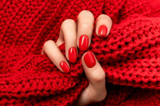 Woman's hand in sweater with red manicure on gray