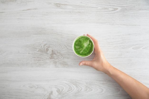 La mano della donna porta via il bicchiere di carta con il latte di tè matcha premium biologico giapponese preparato. sulla tavola di legno bianca. vista dall'alto