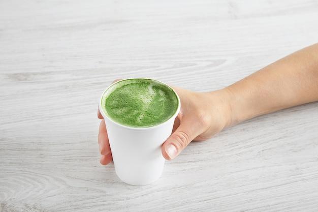 La mano della donna porta via il bicchiere di carta con il latte di tè matcha premium biologico giapponese preparato. sulla tavola di legno bianca.