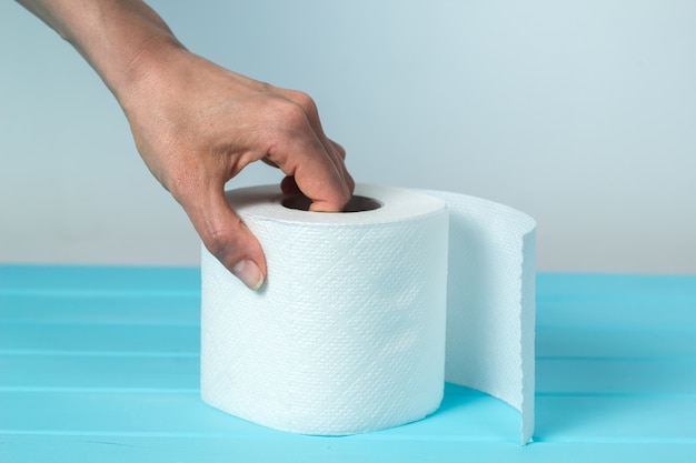 A woman's hand takes a roll of toilet paper. the concept of diarrhea.