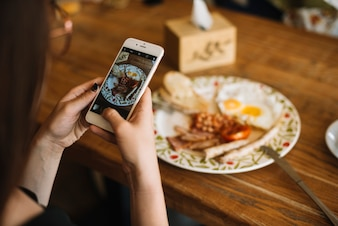 Woman's hand taking photo of breakfast on wooden table through cell phone