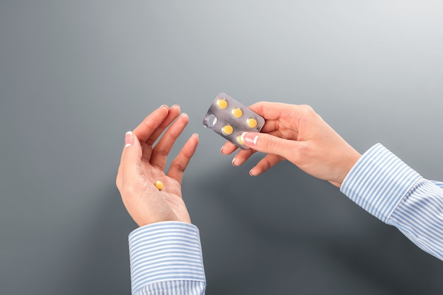 Woman's hand taking pill. woman has abnormal heart rate. this one cures allergy. remember the dosage.