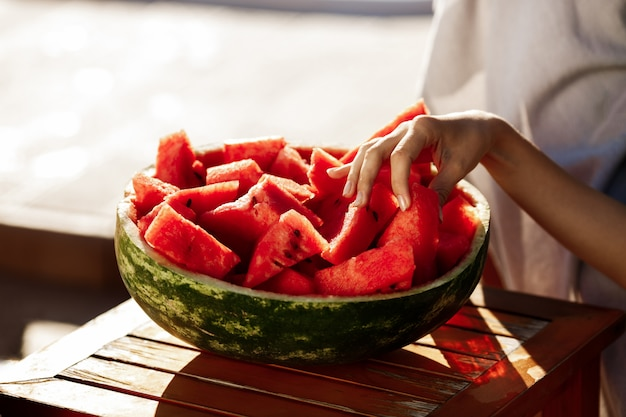 Woman's hand taking watermelon copy space