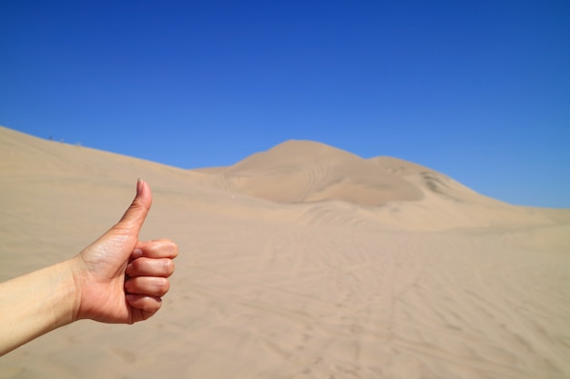 Woman's hand thumbing up to the amazing view of huacachina desert in ica region of peru