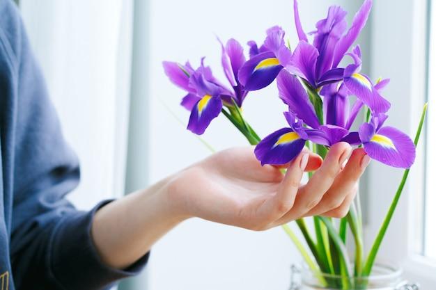 窓辺の花瓶にアイリスに触れる女性の手