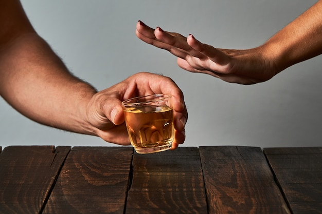 A woman's hand trying to stop her partner from drinking at a bar. concept of alcoholism and drinking addiction.