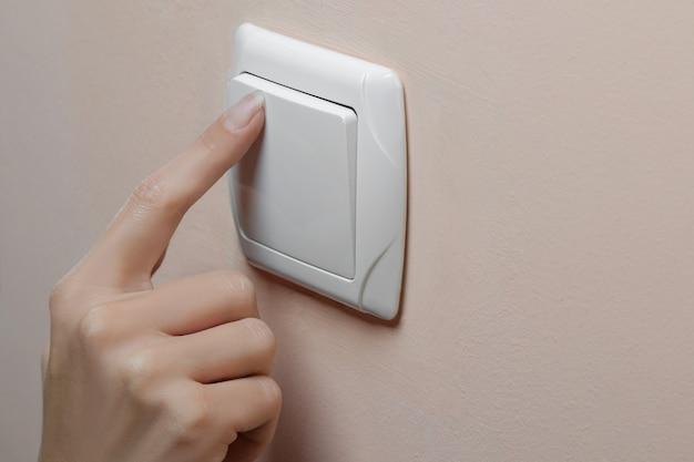 Женская рука выключает свет в комнате