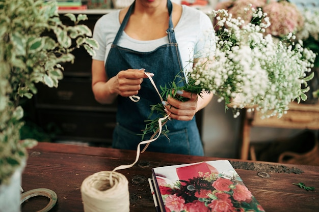 Woman's hand tying bunch of flowers with string in shop
