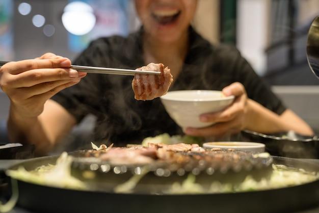 Женские руки используют палочки для еды, содержат корейскую свинину на гриле