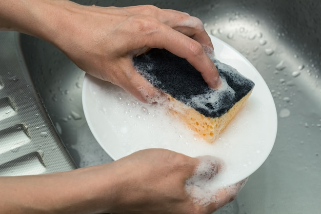 The woman's hand washes the plate in the sink with a sponge. sponge for washing dishes in