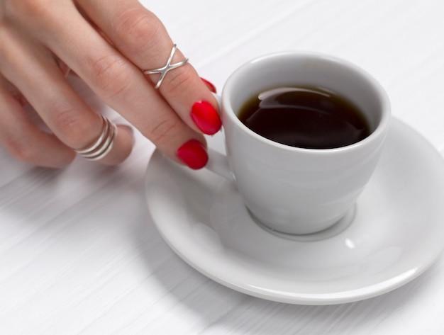 エスプレッソのカップを保持している美しいマニキュアの女性の手。