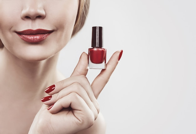 Женская рука с бутылкой красного лака для ногтей. изолированные на белом фоне.