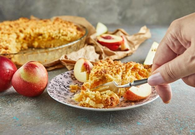 Женская рука с вилкой отламывает кусок пирога с персиками и грушами