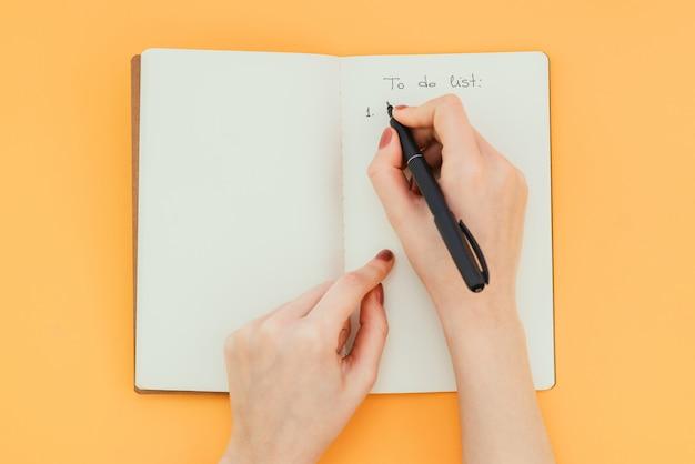 펜으로 여자의 손을 빈 메모장에 할 일 목록을 씁니다.