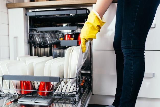 Женская рука с открытой посудомоечной машиной, наполненной чистой посудой.