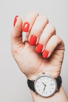 Женская рука с ярко-красными ногтями в серебряных наручных часах
