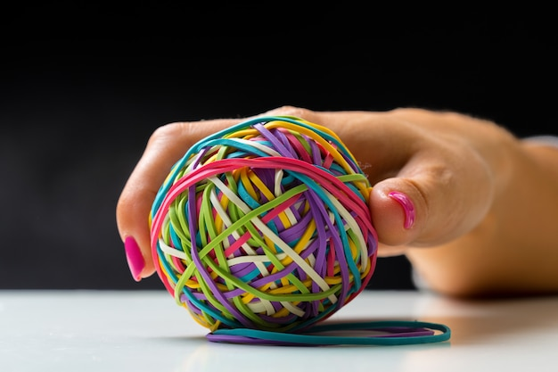 Woman's hand with colorful rubber bands ball