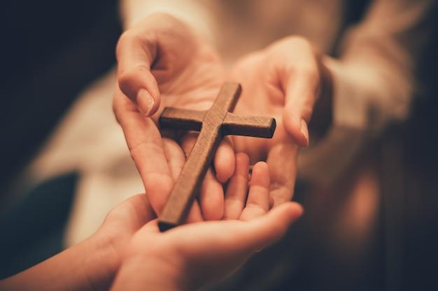 십자가와 여자의 손입니다. 희망의 개념입니다.