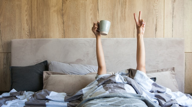 Woman's hand with a cup of coffee in bed, the concept of the beginning of a new day, good morning