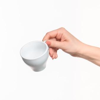 La mano della donna con la tazza sulla parete bianca