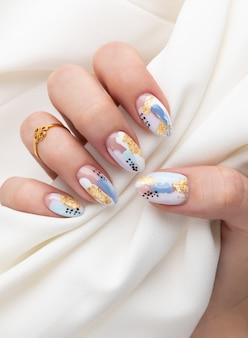 Woman's hand with fashionable nails holding fabric