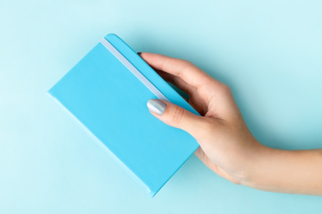 Woman's hand with manicure holding notepad on blue background