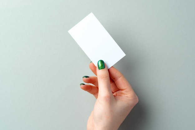 Woman's hand with manicure holding white business card above the table, copy space