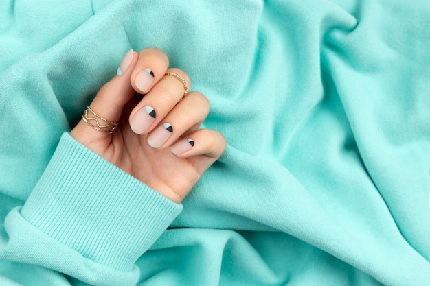Woman's hand with nude and blue matte nail design