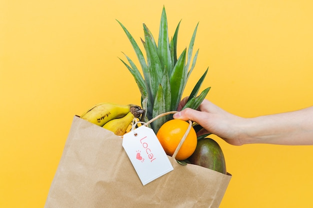 Woman's hand with paper shopping bag with tropical fruit and label with word local on yellow background. copy space.