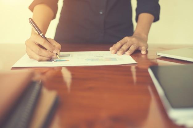 Mano della donna con una scrittura della penna sul foglio di lavoro. rapporto ch