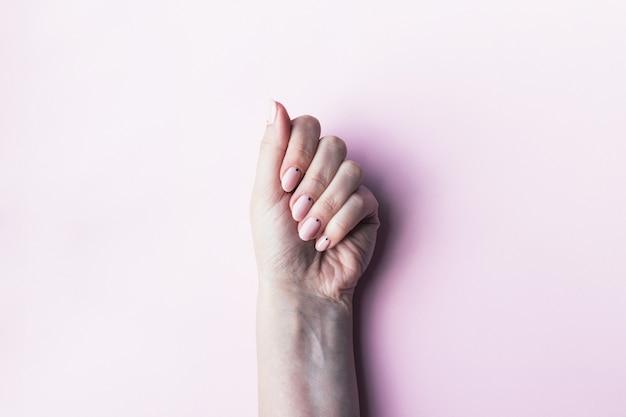 小さな黒い点とピンクの裸の爪を持つ女性の手