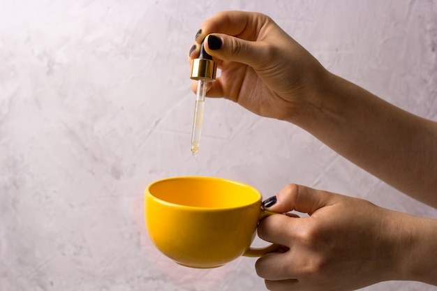 Woman's hand with pipette and mug. liquid vitamins