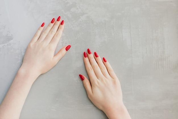 콘크리트 테이블에 빨간 매니큐어와 여자의 손