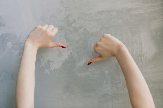 コンクリートのテーブルに赤いマニキュアと女性の手