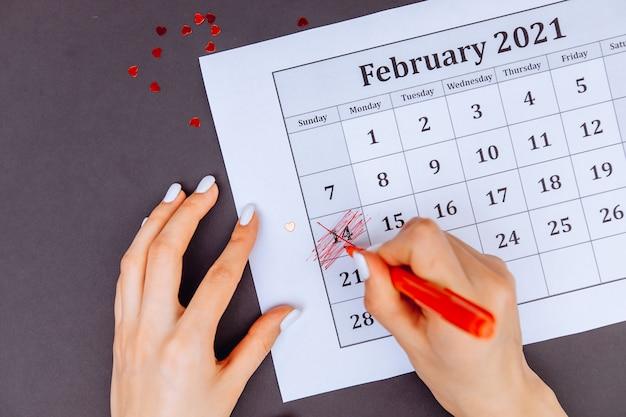 赤いマーカーの付いた女性の手は、バレンタインデーのカレンダーにハートの形を描いてみます。 2月14日のコンセプト。