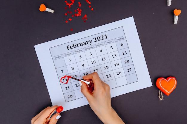 赤いマーカーの付いた女性の手は、バレンタインデーのカレンダーにハートの形を描いてみます。 2月14日
