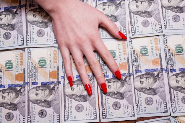 Woman's hand with red nails lying on the money, greed for money, background of the money, hundred dollar bills front side. background of dollars