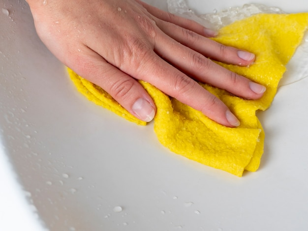 A woman's hand with a yellow cloth washes the sink. the concept of cleaning the house