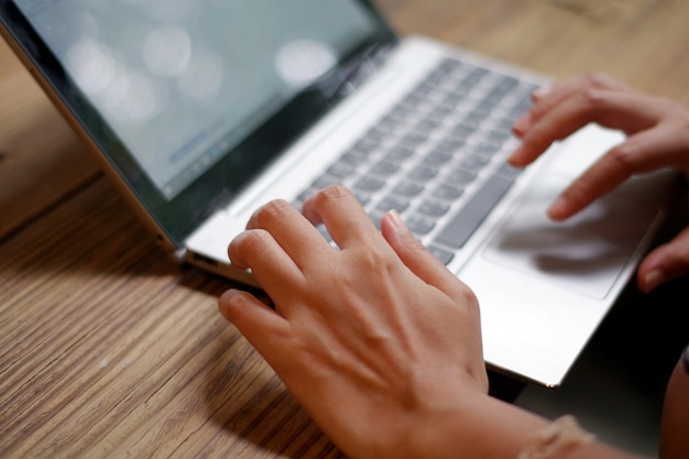 Woman's hand working on keyboard laptop computer on wood table in a cafe