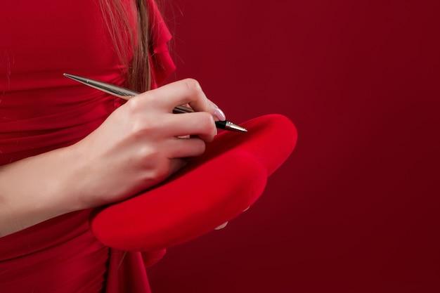 Женская рука пишет ручкой на сердце ко дню святого валентина