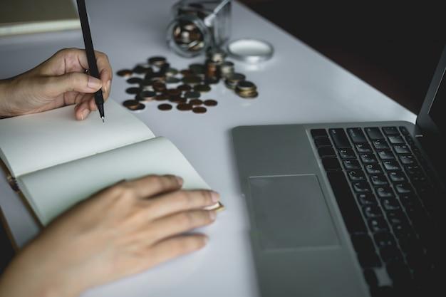 Рука женщины, написание заметки для планирования и экономии денег с монетами в стеклянной банке и компьютер ноутбук для бизнеса и финансов концепции