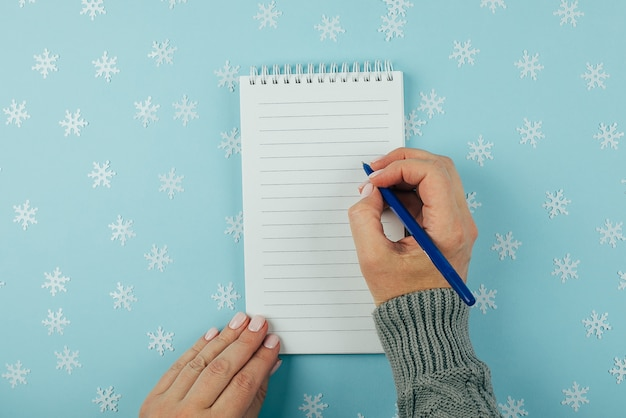 Woman's hand writing in empty notebook decorated with christmas decorations