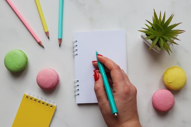 ノートに女性の手書き。ノートブック、鉛筆、ペン、植物、マカロンのあるワークスペース