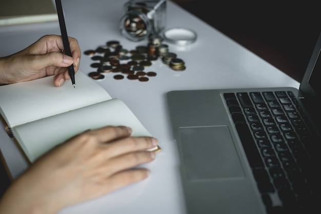 Woman's hand writing a note for planning and saving money with coins in the glass jar and computer laptop for business and finance concept