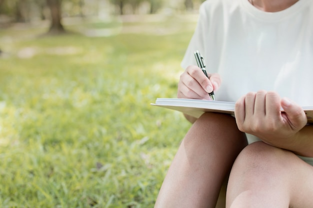 Woman 's hand writing  on notebook on green nature