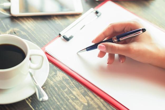 Написание руки женщины на пустой планировщик в кафе.