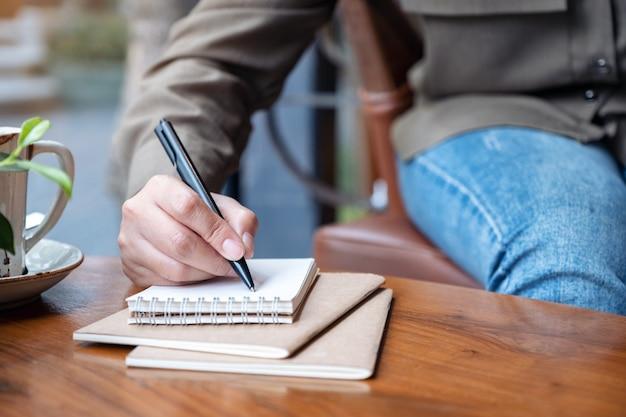 나무 테이블에 커피 컵과 빈 노트북에 쓰는 여자의 손