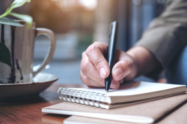 Женский почерк на пустой тетради с кофейной чашкой на деревянном столе