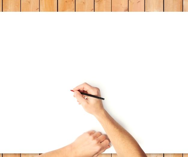 木製の机の上の白い紙に書く女性の手