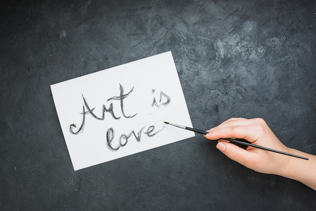 Woman's hand written 'art is love' text on white paper with paintbrush over slate backdrop